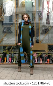 Slim model in a full-length show clothes at the window of a vintage store. She is dressed in a boho style: a green jumpsuit and a long blue scarf.