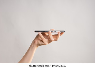 Slim modern smartphone, use the Internet or apps. A woman's hand holds the phone horizontally. light grey background, layout for your design.