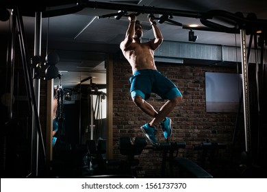 Slim muscular man doing pullups shirtless in the gym, high contrast image