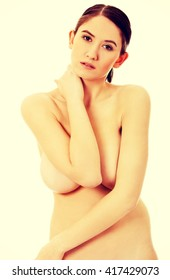 Slim naked woman covering her breast