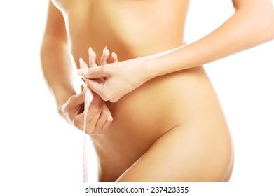 Slim naked woman measuring her waist.