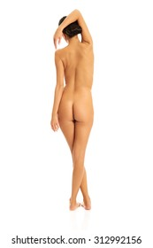 Slim nude woman standing with arm behind head