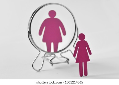 Slim paper woman looking in the mirror and seeing herself as a fat woman - Anorexia and eating disorders concept