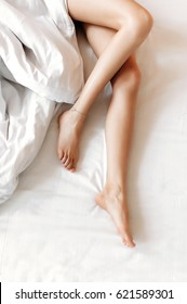 Slim, perfect and beautiful crossed woman legs on bed. Cropped image of erotically lying on bed beautiful woman in bedroom. Crumpled white bedding. Vertical photo, top view.