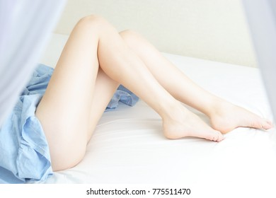 Slim, perfect and beautiful crossed woman legs on bed. Cropped image of erotically lying on bed beautiful woman in bedroom. Crumpled white bedclothes. Horizontal photo