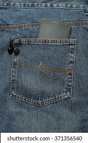 A slim phone and earphones in a back pocket of a jean