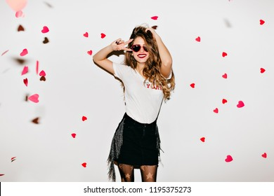 Slim pretty brunette girl dancing on white background. Refined long-haired lady in sunglasses spending leisure time in studio.