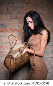 Slim pretty brunette looking something in her handbag