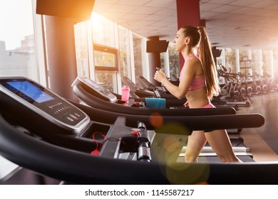slim pretty girl running at the treadmill in the gym against the sunset. Concept of cardio exercises and healthy way of life