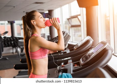 slim pretty joyful girl jogging at the treadmill and drinking a shaker with protein cocktail in the gym against the sunset. Concept of cardio exercises and healthy lifestyle
