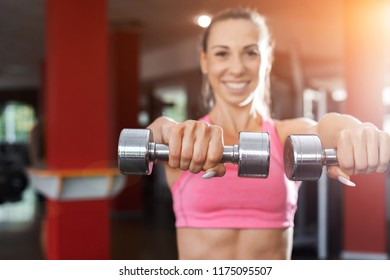 slim pretty smiling girl wearing pink and black sportswear doing exercise using dumbbells in a gym. Strength and motivation concept
