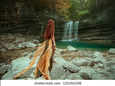 Slim redhead lady in a green yellow lond dress, with a waving train, stands with her back to the camera. Asia princess is looking at the waterfall river lagoon. Without a face. Magic Art photography