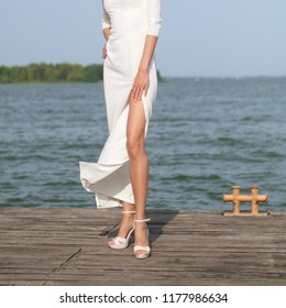 Slim and sexy bare female legs in long evening dress on wooden pier