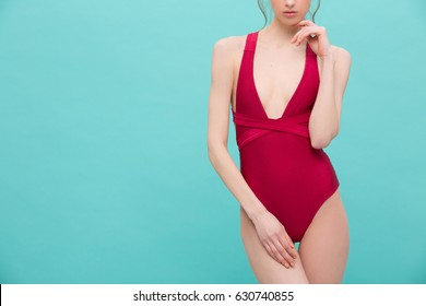 Slim sexy model body in a red wine color body swimsuit posing over mint colour background. Skinny girl in burgundy summer swimwear looking fresh and hot
