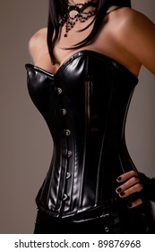 Slim sexy woman with hourglass figure in black leather corset, studio shot