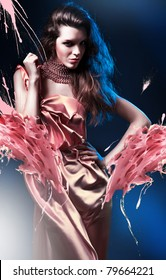 slim sexy woman in pink dress on blue light and splash