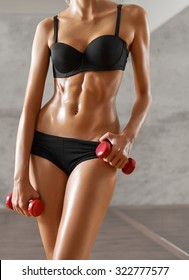 Slim, sexy,blonde, young sportswoman with athletic body, poses with dumbbells, looking in camera, in black sportswear, at the gym. Full-length portrait.