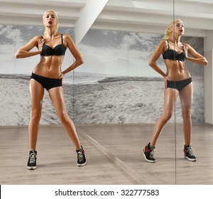 Slim, sexy,blonde, young sportswoman with athletic body, pumped press, poses at the gym, looking in camera, in black sportswear, full-length portrait.