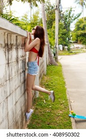 Slim skinny beautiful girl in red bra bikini, trendy sunglasses and short denim shorts trying climb up a stone wall. Urban scene, city life. Cute attractive sexy hipster lady look over high fence.