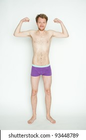 Slim or skinny young man in underpants flexing muscles, isolated on white background