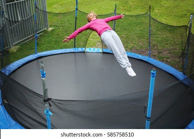 Slim smiling woman jumps on trampoline outdoor at summer day, top view