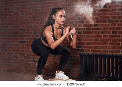 Slim sport woman in sportswear jumping on fit box and do squats. bodybuilding. Brickwall background
