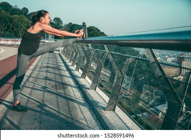 Slim sportswoman putting foot on the banister of the bridge while tying shoelaces
