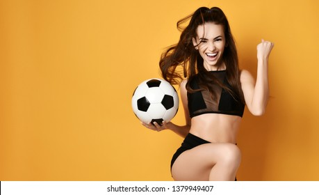 Slim sporty woman player or fan in black uniform with the soccer ball celebrates happily a win and gesticulate actively on yellow background