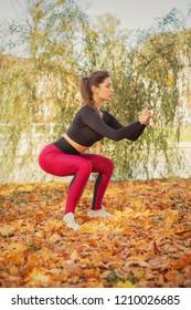 slim sporty woman squat in autumn city park
