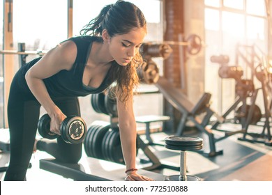 Slim sporty woman working out with dumbbell in the gym.