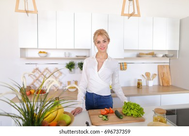 Slim, sweet girl looks away and with beautiful smile on face poses, spreads vegetables on cutting board, standing in middle of stylish and light kitchen equipped with modern technology. Blond female