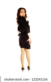 A slim and tall Korean woman standing for white background with her back to the camera and looking over her shoulder in a black dress and heels.