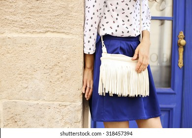 Slim tanned girl in clothes in a marine style. Marine style of dress. White bag with fringe. Indigo blue. Saturated blue. Street fashion. Fashion model. Fashion street look. Items of clothing.