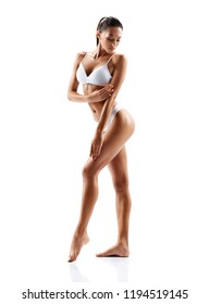 Slim tanned girl in white lingerie posing on white background. Beauty and body care concept