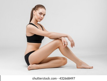 Slim tanned woman body over gray background