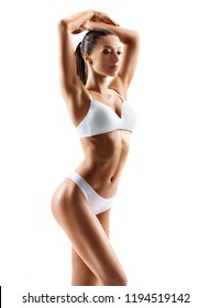 Slim tanned woman's body. Photo of perfect body in white lingerie on white background. Beauty and body care concept