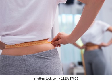 Slim waist. Close up of tender female hands using meter and holding breath