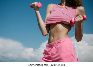 Slim waist. Woman working out with dumbbells on sky background. Fitness waist. Strong abs showing