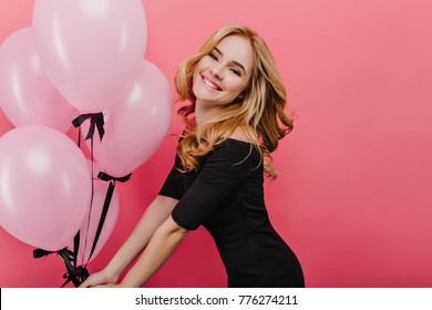 Slim white woman with curly hairstyle celebrating her birthday and happy laughing. Indoor photo of cheerful caucasian girl dancing on pink background in holiday.