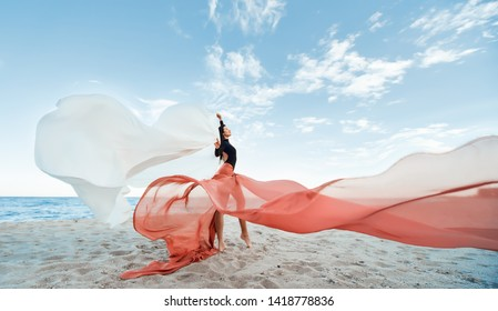 Slim Woman at the beach with long pink fabric. Sky background at the summer. Classic dancer on the nature