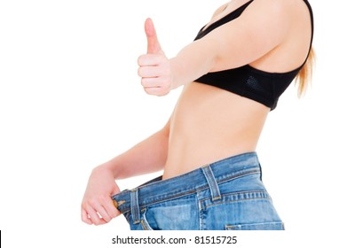 slim woman in big jeans showing thumbs up. isolated on white background