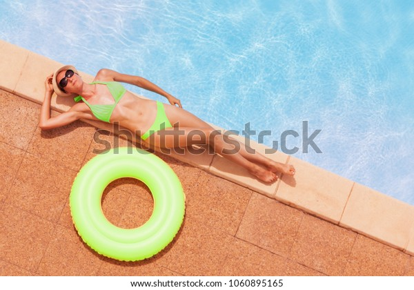 Slim woman in bikini relaxing by the swimming pool