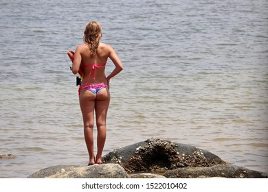 Slim woman in bikini standing with snorkeling equipment on the rocks on sea background. Beach holidays, diving and swimming, tropical coast