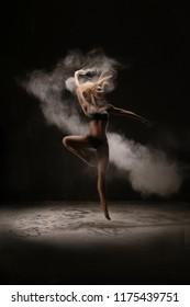 Slim woman dancing in white powder cloud