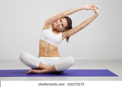 Slim woman exercising on a mat in a gym