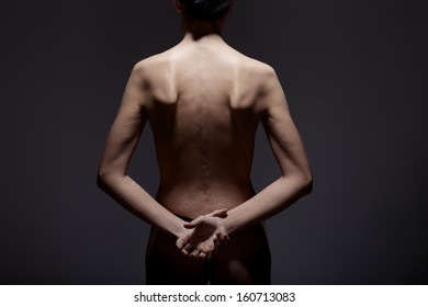slim woman with hands put behind the back
