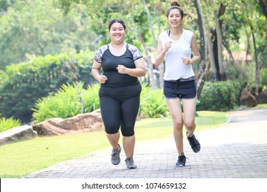 a slim woman help her fat friend to exercise and jogging or running in a park in the morning
