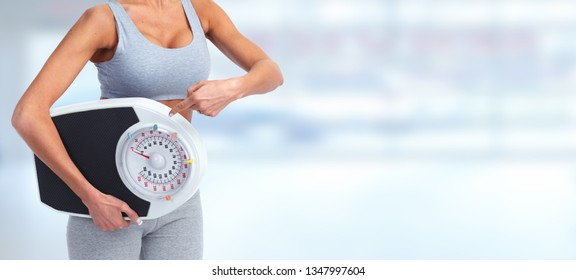 Slim woman holding scales.