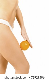 Slim woman holds an orange on her hip.