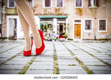 Slim woman legs and red heels